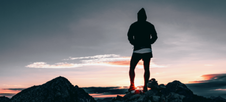 Guy standing on a mountain at sunset: Two Lies Young Men Believe About Porn